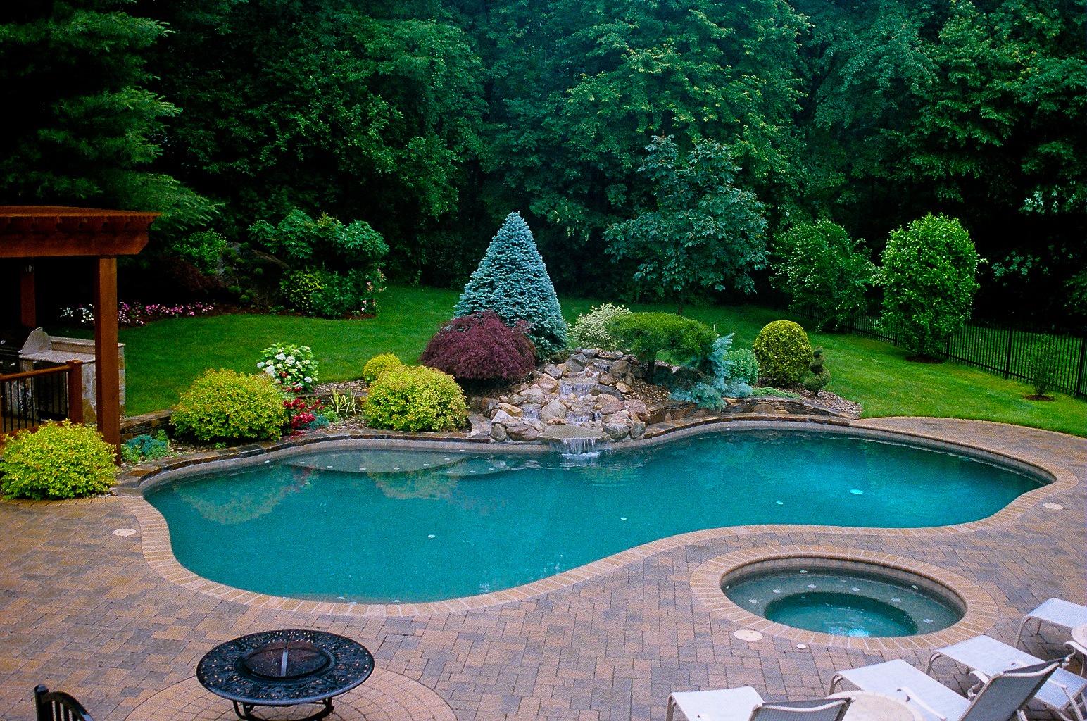 Poolside waterfall with formal planting 2 for Garden pool landscaping